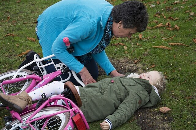 Paediatric First Aid with a lady who is bent over helping a little girl who has fallen off her pink bicycle